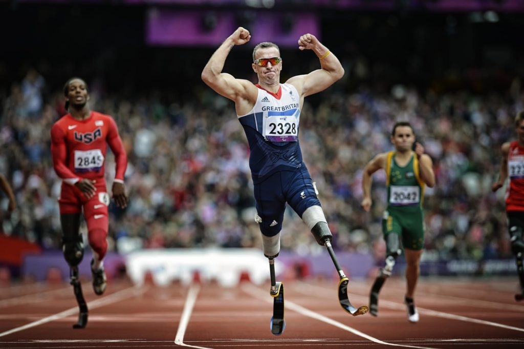 Great Britain's Richard Whitehead (C) crosses the finish line to win the Men's 200 metres T42 Final during the London 2012 Paralympic Games at the Olympic Park in east London on September 1, 2012. AFP PHOTO / ADRIAN DENNIS